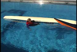 swimmer next to capsized kayak at cockpit