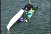 second swimmer does wet re-entry while kayak being held by the first paddler